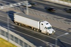 Large truck with a trailer on the highway at a speed that moves along the asphalt, evening sunset light. View from above. Large truck with a trailer on the Royalty Free Stock Photography