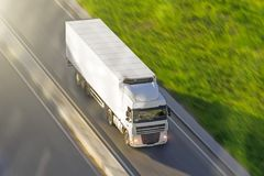 Large truck with a trailer on the highway at a speed that moves along the asphalt, view from above. Large truck with a trailer on the highway at a speed that Royalty Free Stock Images