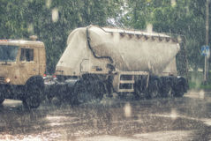 Large truck with a trailer on the road under heavy rainfall Stock Images