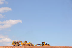 Large trucks moving dirt. A view of two large earth moving equipment hauling dirt on a construction site under sunny blue skies royalty free stock photography