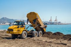 Large trucks restore sand on the coast expanding the beach. Malaga, Spain - April 17, 2018. Large trucks restore sand on the coast expanding the beach Huelin Royalty Free Stock Photography