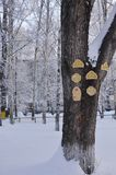 A large trunk of snow-covered wood on which are made of plywood round, carved Windows and doors for children to play. stock photography