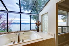 Large tub with glass wall with water view. Large tub with beige tiles and glass wall of windows stock photography