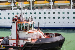 Large Tugboat by Cruise Ship Royalty Free Stock Photo