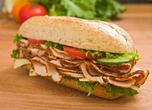Large turkey breast sandwich on a wooden surface