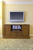 Large tv above wooden stereo cabinet. Large wall mounted television hanging above wooden stereo cabinet containing electronic equipment Stock Photography