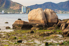 Large twins stones in shallow sea against distant resort city Stock Photos