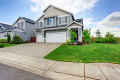 Large two story house with siding, two garage spaces and concrete driveway Stock Image