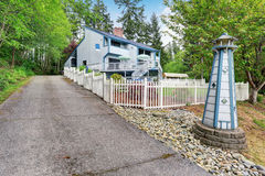 Large two story marine style home with long concrete driveway. Stock Photos