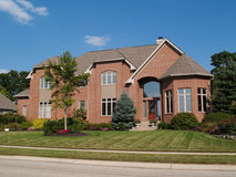 Large Two Story New Brick Home With Turret. Large two story new red brick residential home with a turret at the corner Royalty Free Stock Photos