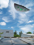 Large UFO. UFO houvering over a house during the day Royalty Free Stock Images