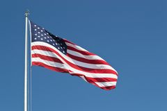 Large United States Flag Horizontal. Large United States flag in horizontal format with bright blue sky. This flag presides over a veteran's memorial in stock photos