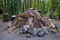 Large unlit camp fire. Large campfire before being lit, composed of oak and bamboo, surrounded by rocks in a tropical bamboo setting Royalty Free Stock Photography