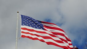Large US flag on a background of gray sky. Beautifully illuminated by the sun stock video footage