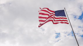 Large US flag on a background of gray sky, beautifully illuminated by the sun. 4K video stock video