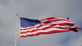 Large US flag on a background of gray sky, beautifully illuminated by the sun