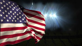 Large usa national flag waving. On black background with flashing lights stock video footage