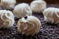 Large vanilla marshmallows. Sweet dessert - large vanilla marshmallows  on a wooden table with coffee beans, selective focus Royalty Free Stock Photos