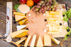 Large variety of cheeses displayed around a board Stock Images
