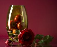 Large vase with fruits and single flower on maroon Stock Photography