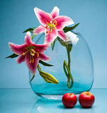 Large vase with two flowers and fruits on blue Royalty Free Stock Photos