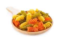 Large vegeroni Rotini spirals pasta in wooden plate on white. Background stock photos