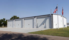 Large Vehicle Garage and Storage Building. White garage and storage building for large vehicles and equipment of the community with American flag flying outside Stock Photo