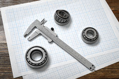 A large vernier scale lying on cross section paper with three bearings around it on wooden background. Stock Photography