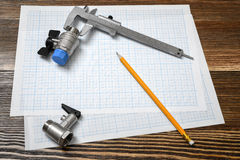 A large vernier scale lying on cross section paper with two ball valves and a pencil lying beside on wooden table Royalty Free Stock Photography