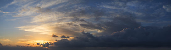 Large vibrant panorama image of stormy sunset sky Stock Photo