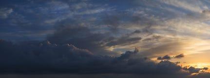 Large vibrant panorama image of stormy sunset sky Stock Photo