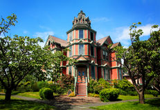 Large Victorian Mansion. Street view of a beautiful large old luxurious victorian home with lots of gingerbread trim, a turret and a lot of windows under blue Stock Photo