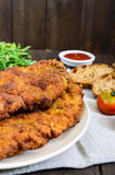 A large Viennese schnitzel on a dark wooden background. stock image