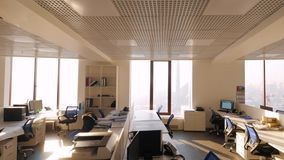 Large view of call center outside working hours. Modern empty office with open plan and large windows. Off-hours in. Office overlooking the skyscrapers on sunny stock footage