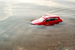 Large view of a red toy car that drowned under water sticking one roof, green water and sand on the sea. Summer day stock photo