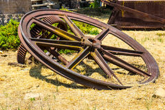 Large Vintage Mining Wheels With Ore Cart Carrier In Background. Vintage Mining Wheels With Ore Cart In Background royalty free stock images