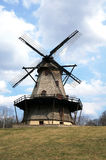 Large Vintage Rustic Windmill. A large windmill at the top of a hill, outside on the grass stock image