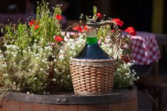 Large Vintage Wine Bottles in wicker basket on a barrel. Autumn still life with a bottle of wine and flowers royalty free stock photography