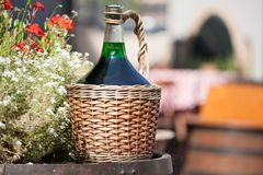 Large Vintage Wine Bottles in wicker basket on a barrel. Autumn still life with a bottle of wine and flowers royalty free stock image