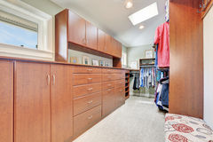 Large walk-in closet with cabinets and carpet floor Royalty Free Stock Image