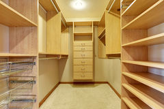 Large walk in closet with hardwood floor, also including many shelves Stock Photography