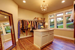 Large walk in closet with hardwood floor. Large walk in closet with hardwood floor and an island royalty free stock photo