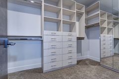 Large walk-in closet with white shelves, drawers. Large walk-in closet lined with built-in drawers, clothes rails and shelving over light brown carpet floor royalty free stock images