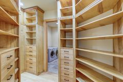 Large walk-in closet lined with built-in drawers. Clothes rails and shelving over light wood floor royalty free stock photography