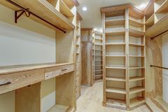 Large walk-in closet lined with built-in drawers. Clothes rails and shelving over light wood floor royalty free stock photos
