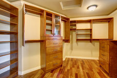 Large walk in closet with many shelves and drawers. Large walk in closet with hardwood floor, also including many shelves and drawers Royalty Free Stock Photos