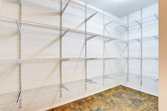 Large walk in closet with tile floor, also including many shelves. Northwest, USA Royalty Free Stock Photo