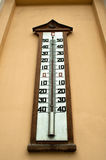 A large wall-mounted mercury temperature gauge. Outdoors Stock Photos