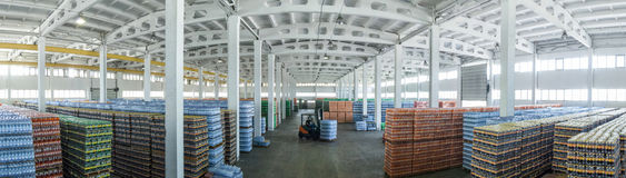 Large warehouse with drinks. Panoramic view of a large warehouse with drinks in plastic bottles with loading machines Stock Photos