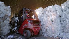 Large warehouse of waste paper in a factory. Loader sorts the pallets with the recycled material at the waste processing plant. Warehouses with recyclable stock footage